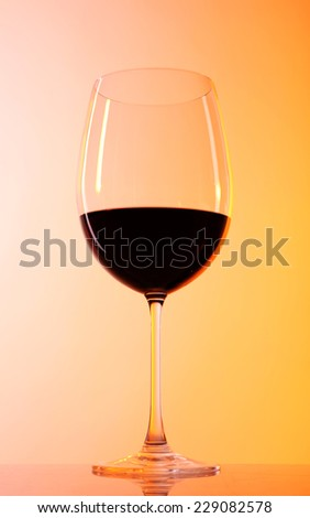 Wineglass with red wine on colorful background