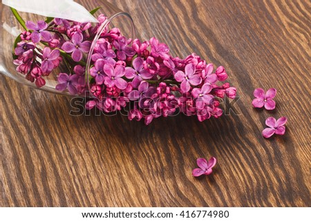 Wineglass with violet lilacs on the wooden background - stock photo
