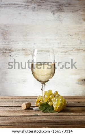 Wineglass with white wine on wooden table - stock photo