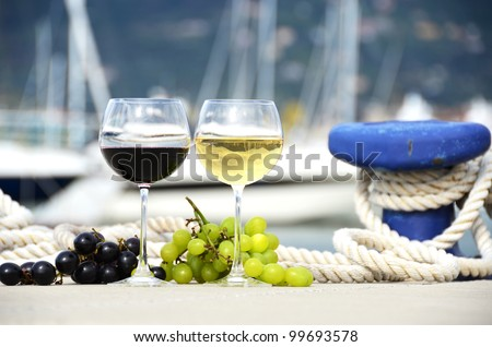 Wineglasses and grapes on the yacht pier of La Spezia, Italy - stock photo