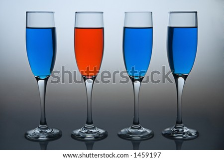 Wineglasses filled with colored liquid - illustrating concepts such as Workplace Diversity or Deomocrat versus Republican. - stock photo