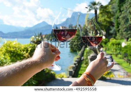 Wineglasses in the hands against lake Como, Italy