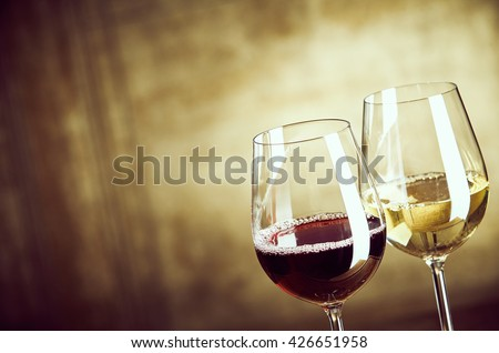 Wineglasses of red and white wine standing side by side in the corner over an abstract rustic brown background with copy space
