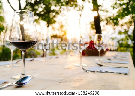 wineglasses on prepared table outdoor - stock photo