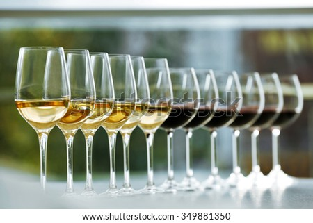 Wineglasses with white and red wine on wooden table on bright background - stock photo