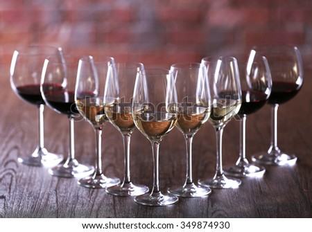 Wineglasses with white, red and pink wine on wooden table close-up - stock photo