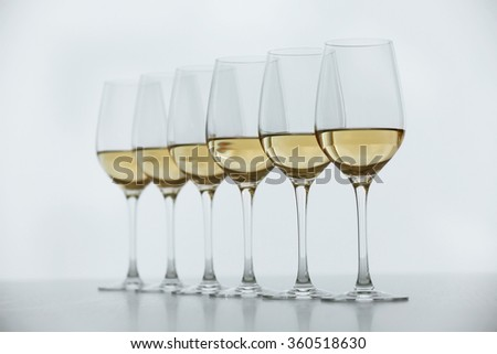 Wineglasses with white wine on wooden table on bright background - stock photo
