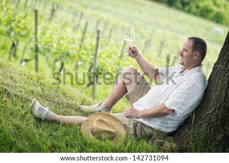 winemaker tasting a glass white wine in the vineyard