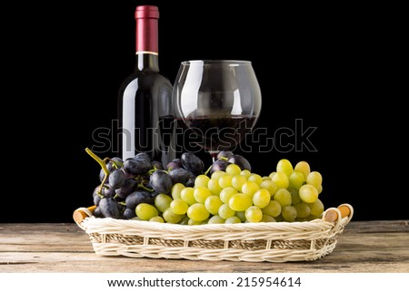 Winery still-life. Different varieties of grapes with wineglass and bottle of white wine on black background