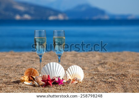 Wines glasses,shells,starfishes on a beach - stock photo