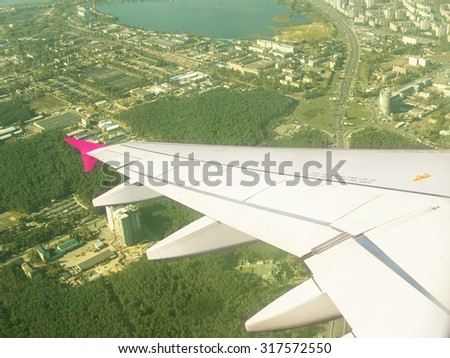 Wing aircraft in aviation window. View of the city, green forest and lake through the aircraft window. Aircraft flying over the green forest and the city, Europe. The airplane is taking off over city. - stock photo