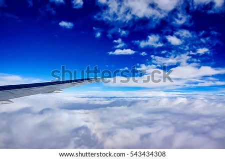 Wing and engines of an airplane flying above clouds during the day.