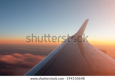 Wing of a Airplane at sunset with clouds - stock photo