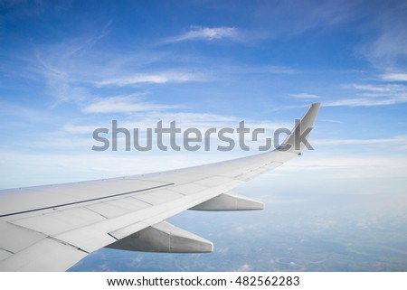 Wing of a plane and blue sky with cloud