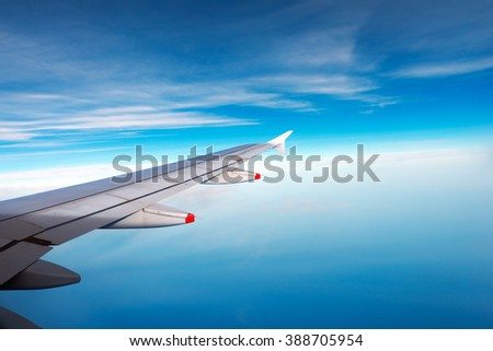 Wing of a plane over the blue sea with blue sky and clouds - stock photo
