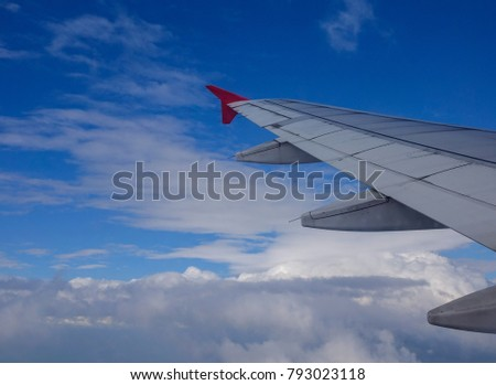 Wing of aircraft with blue sky in sunny day.