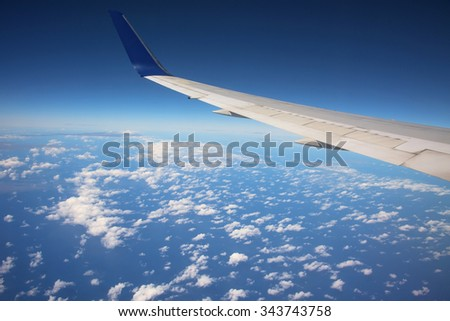 Wing of airplane above many white clouds from window - stock photo