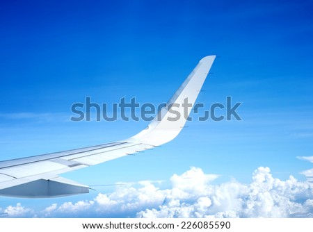 Wing of airplane flying above the clouds and blue sky - stock photo