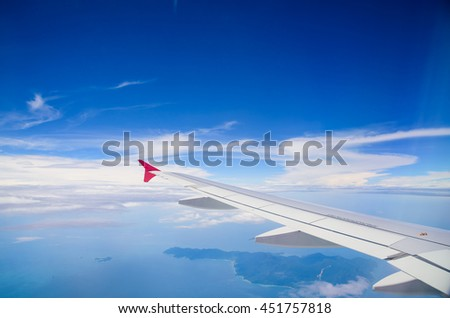 Wing of airplane flying above the clouds in the blue sky background.