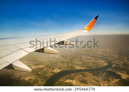 Wing of airplane flying above the clouds in the sky - stock photo