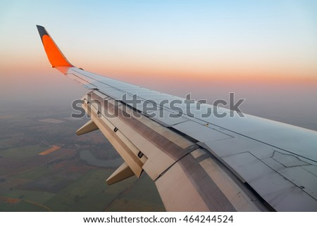 Wing of airplane flying above the clouds in the sky sunset