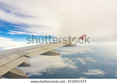 Wing of airplane from window blue sky white cloud, Travel background