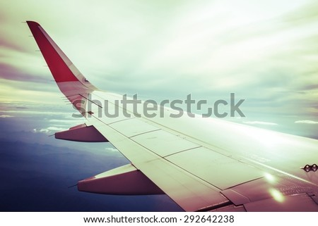 wing of airplane on cloud sky with filtered color,vintage and retro color tone. - stock photo