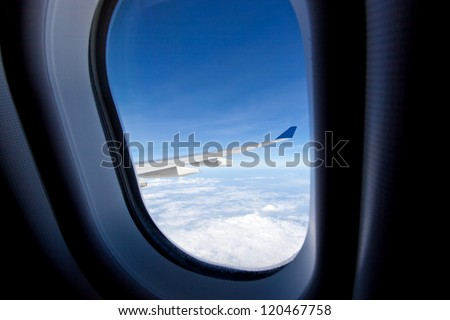 Wing of airplane, view through the window - stock photo
