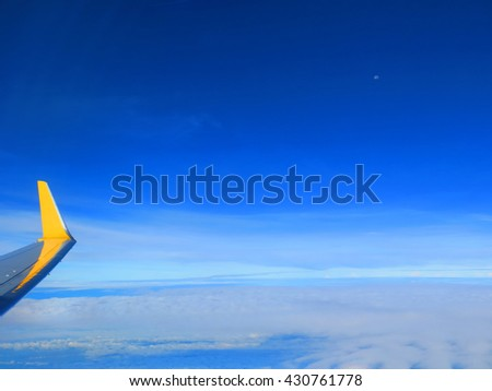 Wing of airplane with blue sky and cloud in the background