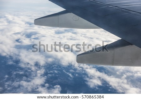 Wing of an aircraft and cloudy sky