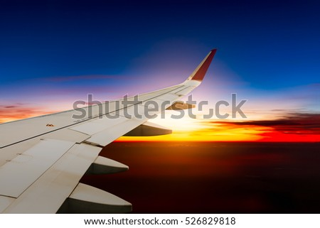 Wing of an airplane above cloud at sunset.