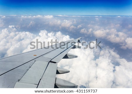 Wing of an airplane cruising above the cloud
