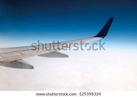Wing of an airplane cruising above the clouds