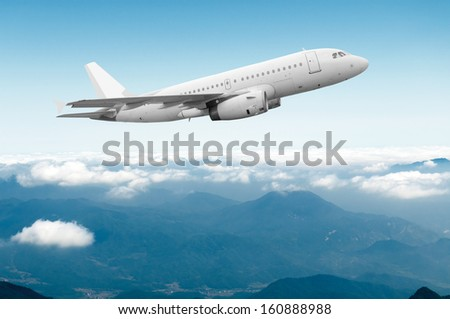 Wing of an airplane cruising above the clouds - stock photo