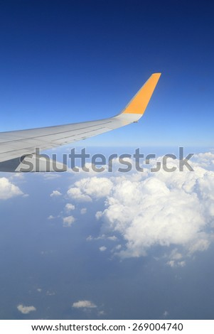 Wing of an airplane flying above sky - stock photo