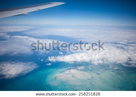 Wing of an airplane flying above the clouds. - stock photo
