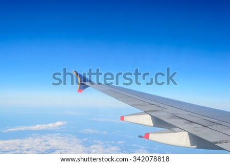 Wing of an airplane flying above the clouds and blue sky background