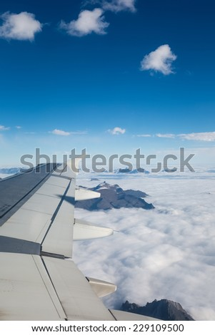 wing of an airplane flying above the clouds and mountains