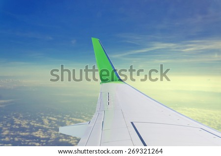 wing of an airplane flying above the clouds, view from the airplane window - stock photo