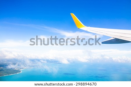 Wing of an airplane flying above the ocean - stock photo