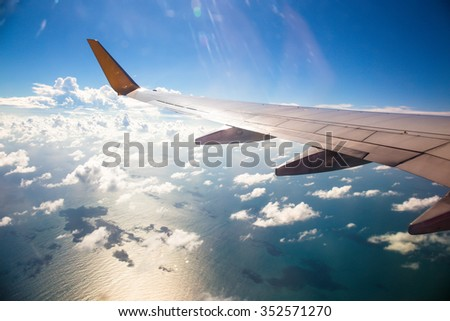 Wing of an airplane flying above the ocean with sunlight over wing