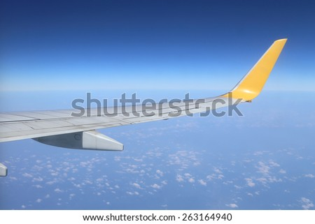 Wing of an airplane flying above the sky - stock photo