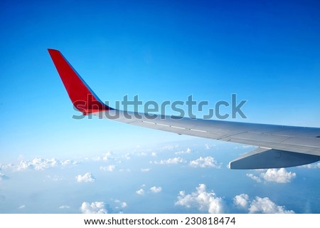 Wing of an airplane flying on Sky with cloud