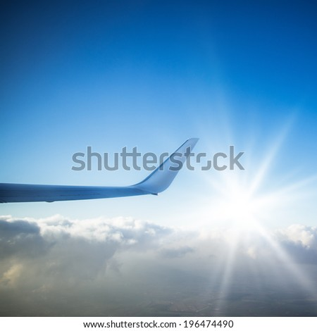 Wing of an flying airplane - stock photo
