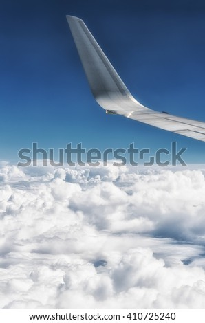 Wing of plane with white clouds below
