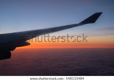 Wing of the air plane on the sea of clouds sunset sky background from window airplane