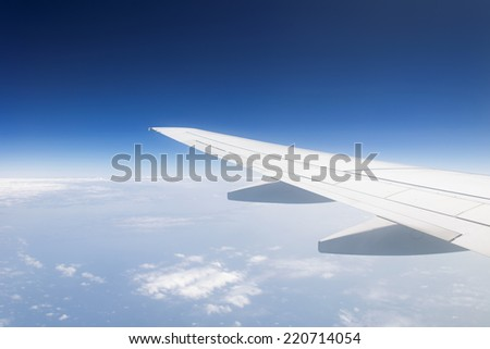 Wing of the plane in cloudless blue sky  background in the middle of a day. copy space. horizon.