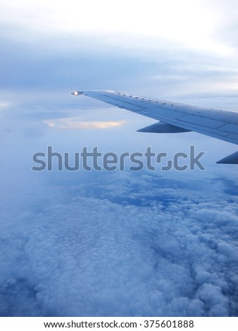 wing of the plane in the cloudy sky - stock photo