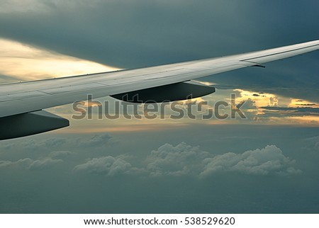 Wing of the plane on a background of sky.White clouds and blue sky view from airplane window. Beautiful cloudscape from sky aerial view. Beauty of nature view from above the sky and clouds.