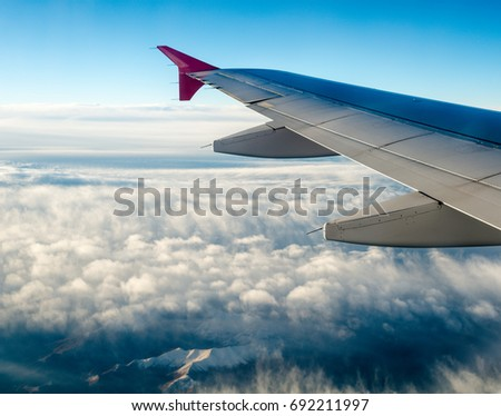Wing of the plane on blue sky and mountains landscape background.